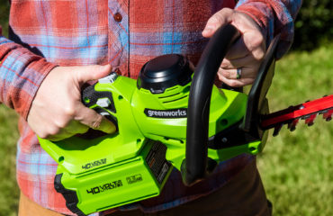 The Greenworks 40V Cordless Brushed Hedge Trimmer cutting through hedges