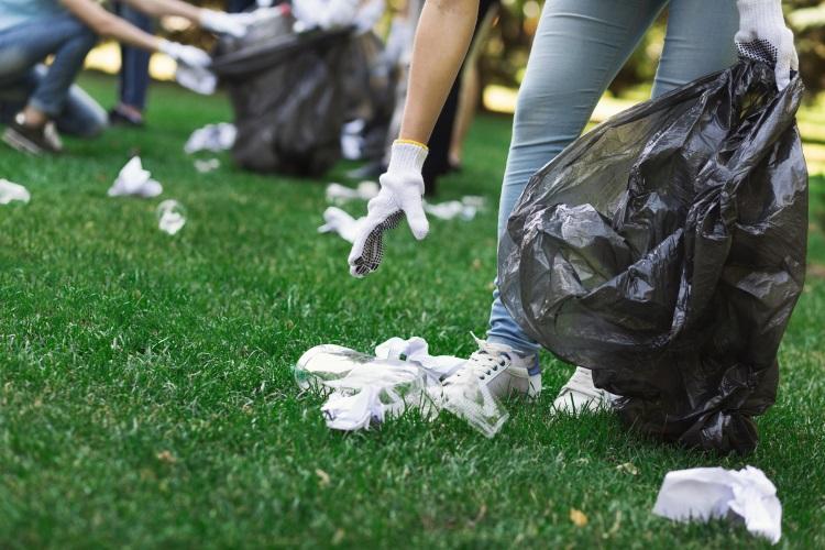 Woman picking up debris in garden