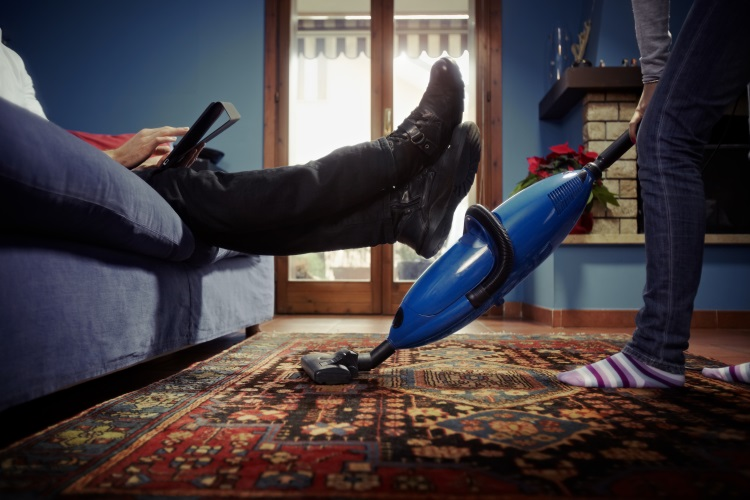 Man Relaxing While Wife Vacuums