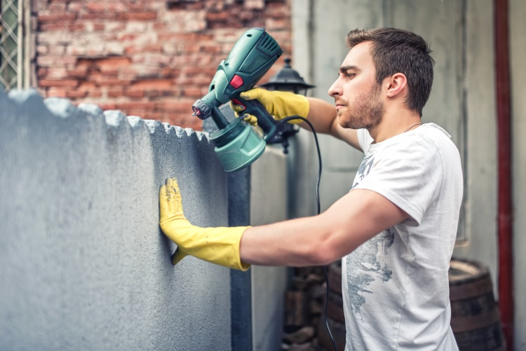 Man Using Spray Gun for Painting
