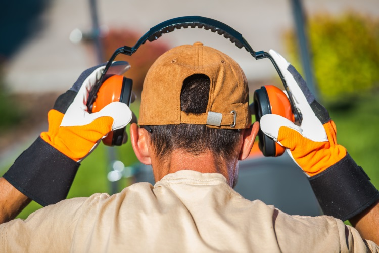 Man wearing ear protection in garden