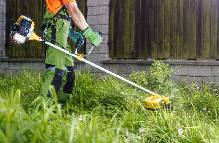 Man with petrol strimmer in garden