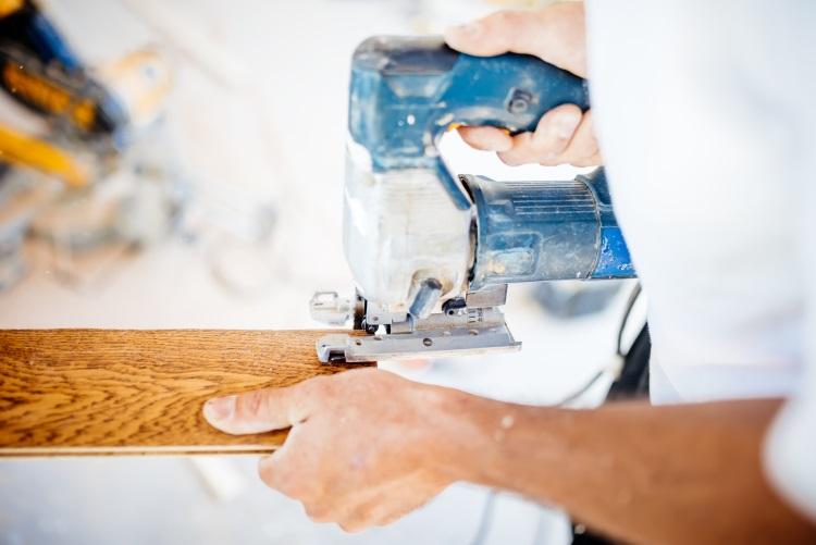 Man cutting piece of wood with jigsaw