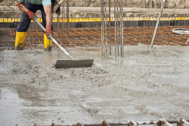 Man laying foundations for shed building