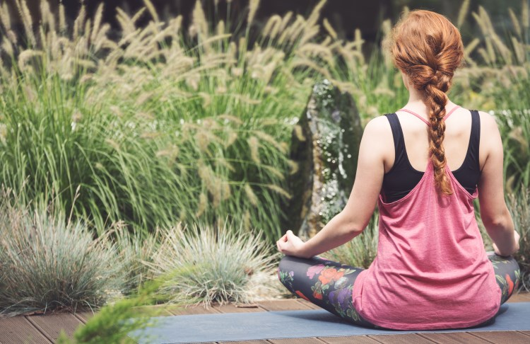 Woman meditating in garden