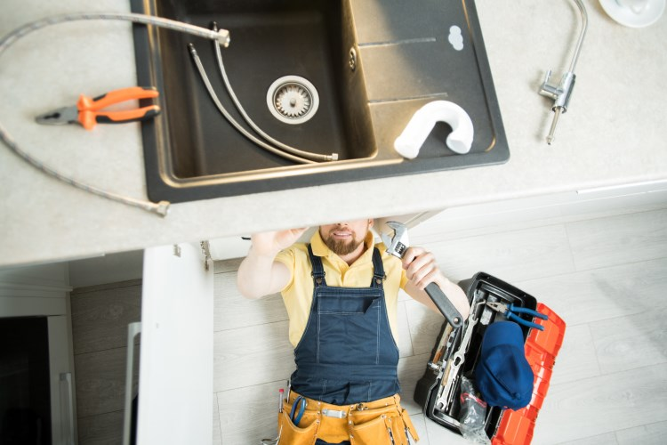 male plumber working on kitchen sink