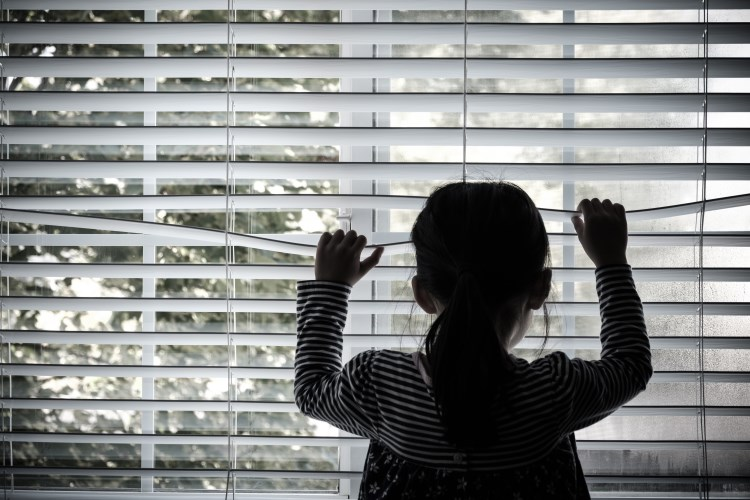 Girl looking out of blind