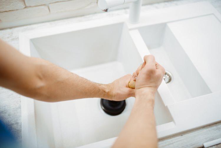 Man using plunger on sink