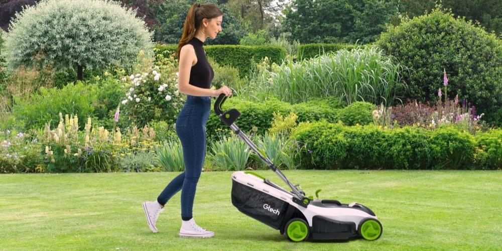 Lady pushing GTech lawnmower